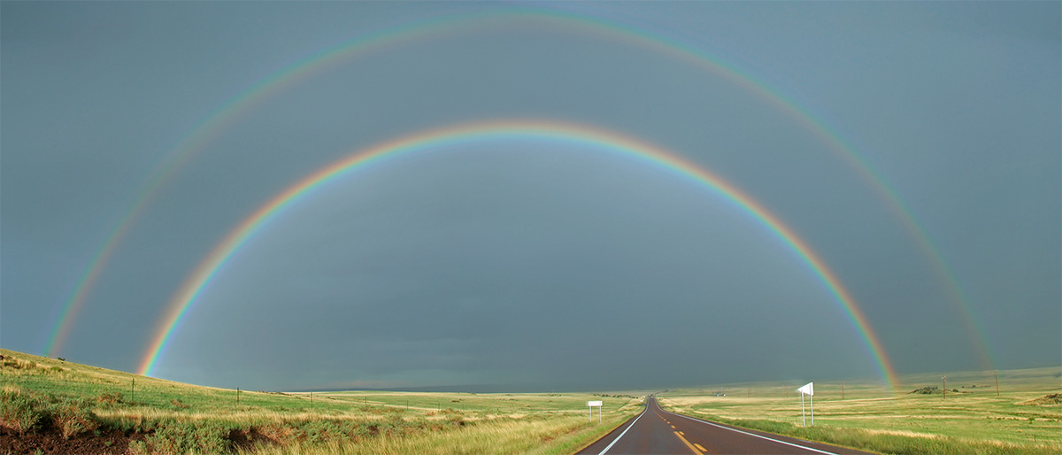 A full rainbow stretching from side to side across the landscape in northern Arizona west of Springerville