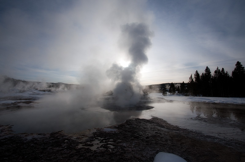 Low morning sun obscured by the rising steam of Castle Geyser on the Upper Geyser Basin in Yellowstone National Park January 2010