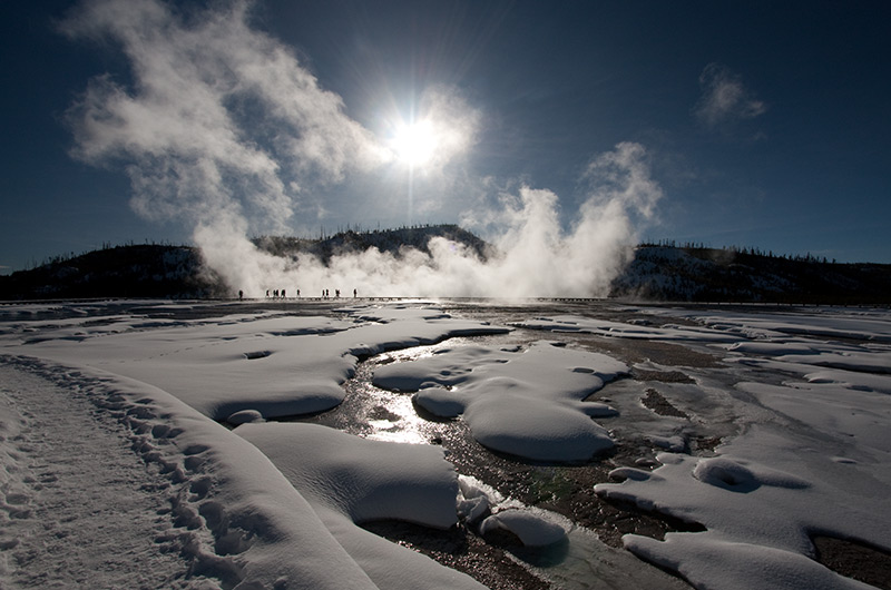 Steam rising from Grand Prismatic Spring with the sun in the background at Midway Geyser Basin in Yellowstone National Park January 2010