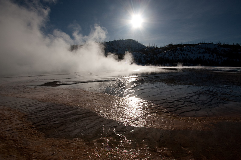 Grand Prismatic Spring with reflective water foreground and sun overhead on winter day at Midway Geyser Basin in Yellowstone National Park January 2010