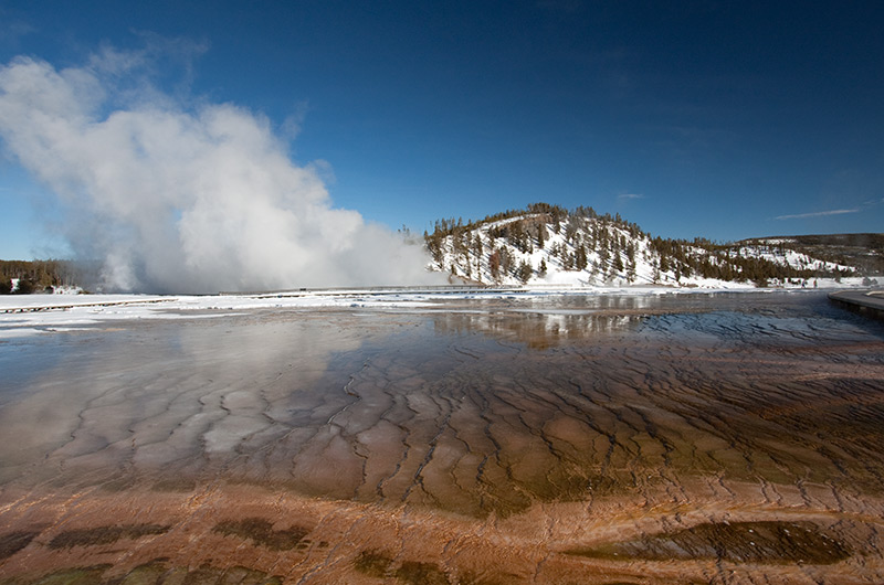Water from Grand Prismatic Spring flowing towards Excelsior Geyser on the Midway Geyser Basin in Yellowstone National Park January 2010