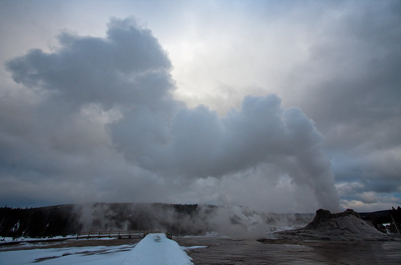 The rising steam of the erupting Castle Geyser against a late afternoon sky on the Upper Geyser Basin in Yellowstone National Park January 2010