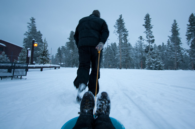 John Wise pulling Caroline Wise in a sled at Yellowstone National Park January 2010