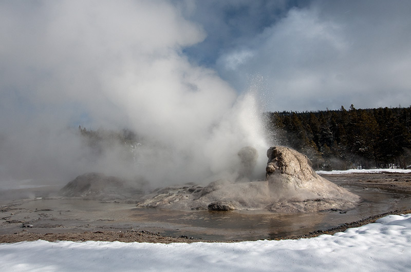 Grotto Geyser erupting on a snowy sunny moment on the Upper Geyser Basin in Yellowstone National Park January 2010