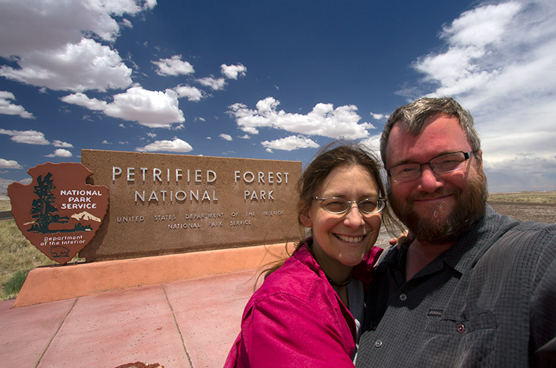 Caroline and John Wise in front of the Petrified Forest National Park sign - Arizona