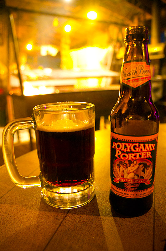 A bottle of Polygamy Porter beer with the swinging grill from the Mexican Hat Lodge in the background