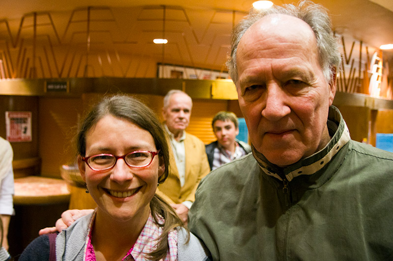 Caroline Wise and Werner Herzog in Tempe, Arizona with Cormac McCarthy in the background following a talk by Stephen Hawking