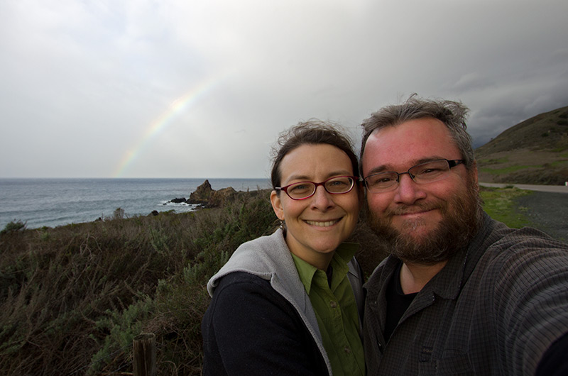 Caroline Wise and John Wise on the California coast under a rainbow