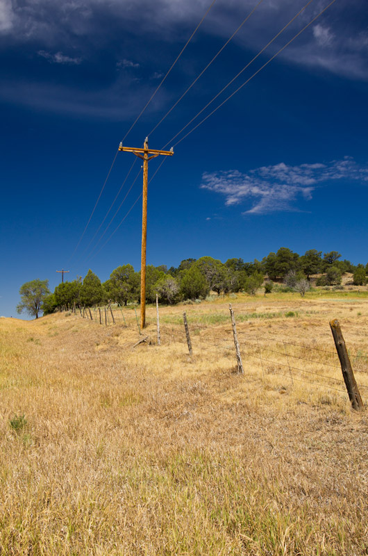 A telephone pole next to barbed wire fence in the dry grass with a deep blue sky