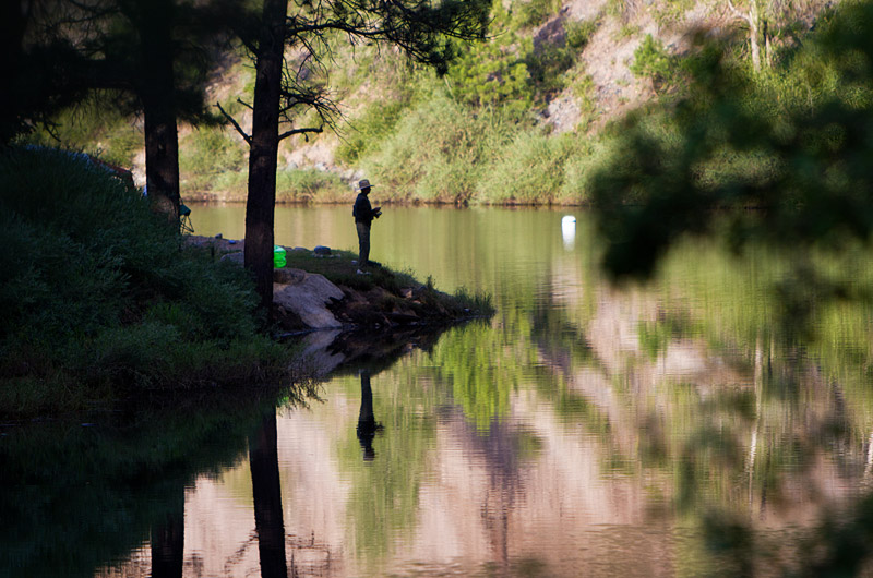 A man fishing next to the reflective waters of Vallecito Reservoir near where the waters of the Los Pinos River enter the reservoir