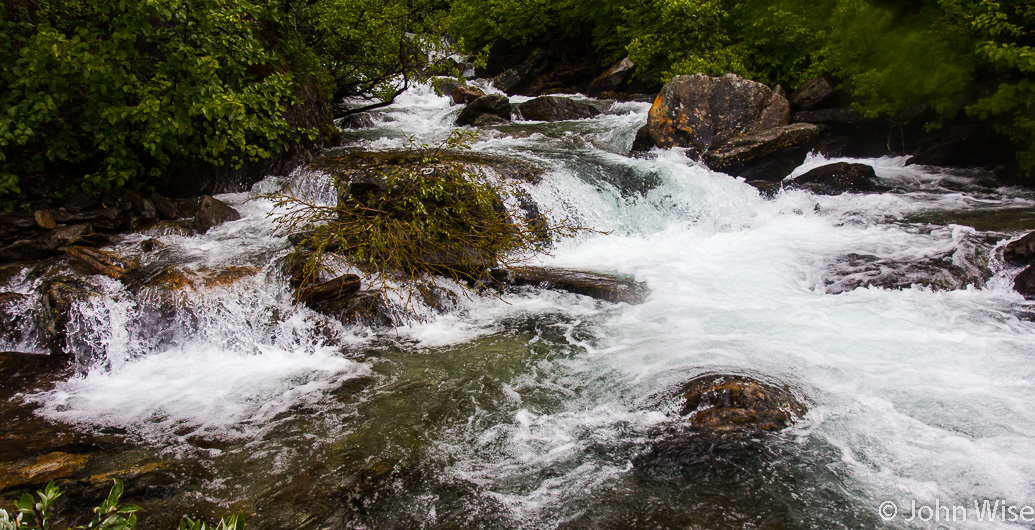 Collecting fresh water from a mountain stream crashing into the Alsek River in Alaska