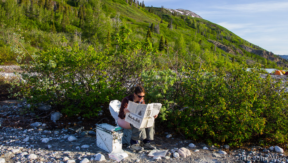 Caroline Wise reading the paper early in the morning while taking care of business in Kluane National Park Yukon, Canada